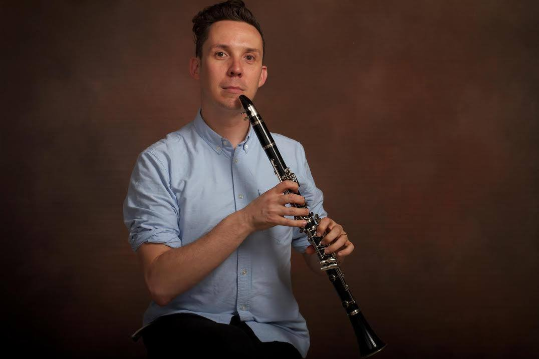man poses awkwardly with flute