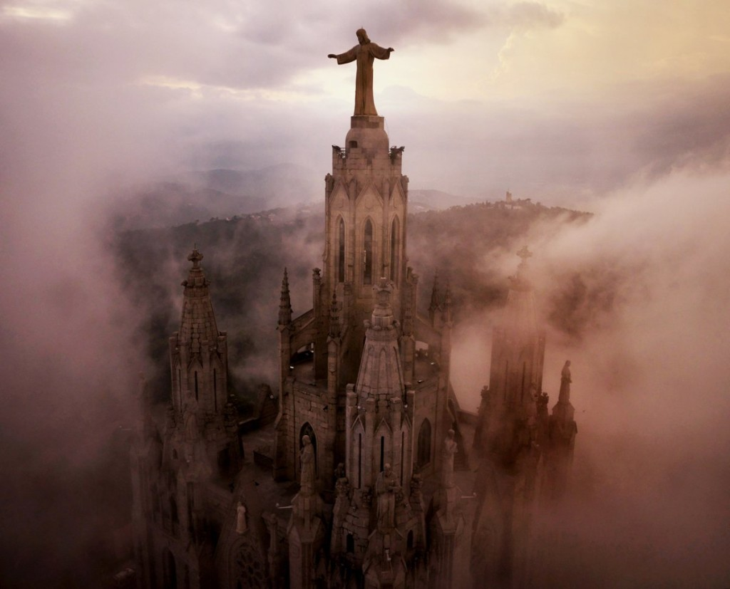 moody aerial shot of clouds swirling through Sagrat Cor Church in Barcelona